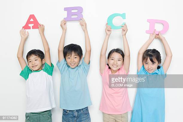 Boys and girls holding alphabet mats