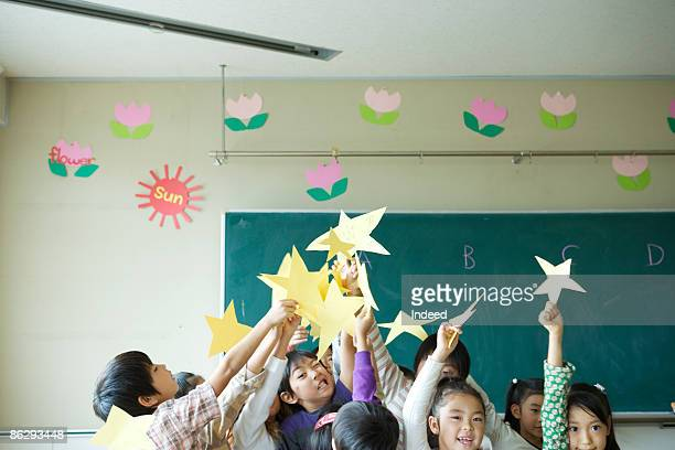 Boys and girls holding stars in classroom