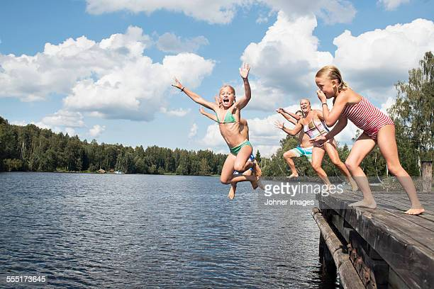 Boys and girls jumping into water