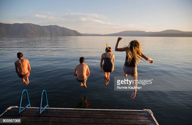 Boys and girls jumping off a dock into lake