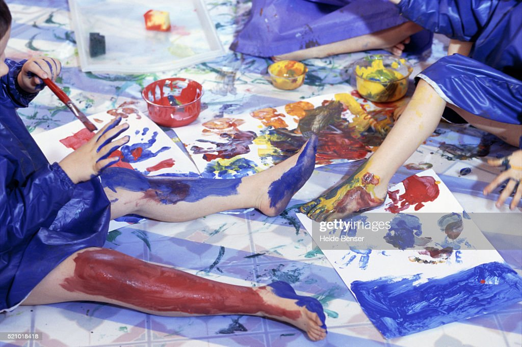 Boys and girls painting with fingers in nursery school : Stock Photo