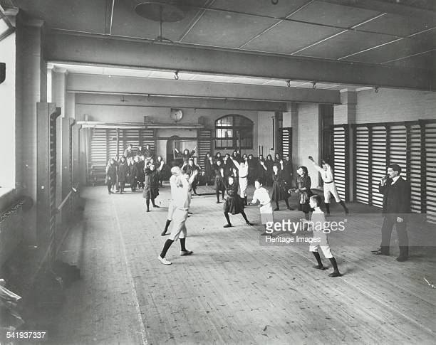 Boys and girls playing netball, Cable Street School, Stepney, London, 1908. A mixed group of boys and girls playing in a gymnasium, refereed by a...