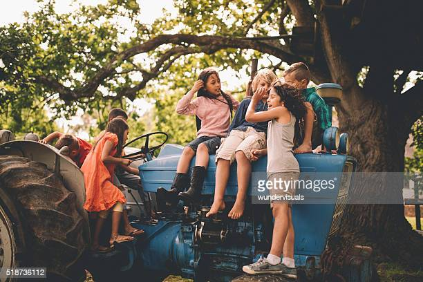 Boys and girls playing on an old tractor under tree