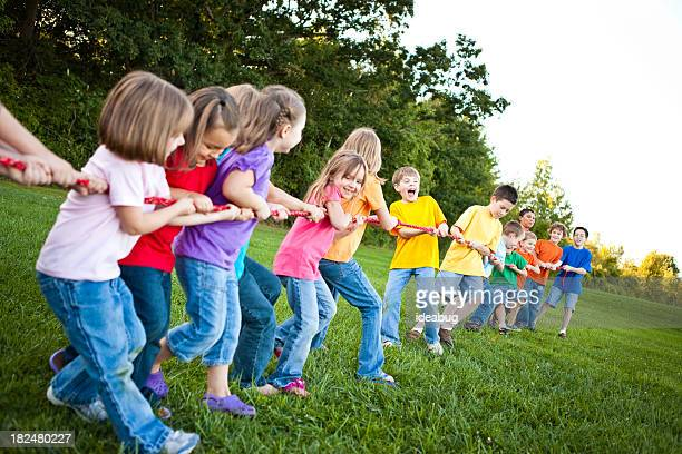 Boys and girls playing tug-of-war on the grass