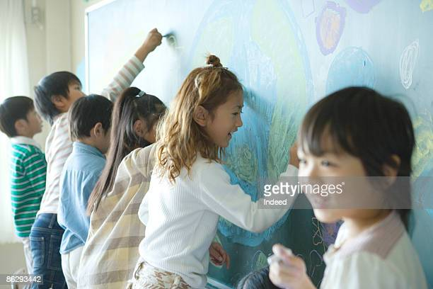 Boys and girls scribbling on blackboard