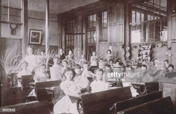 Boys and girls sit at desks and display rattan baskets and home decorations, which they wove during a Vacation School class, New York City.