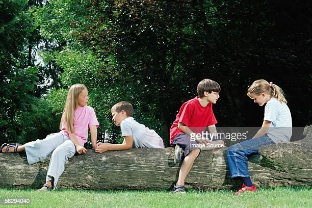 Boys and girls sitting on a log