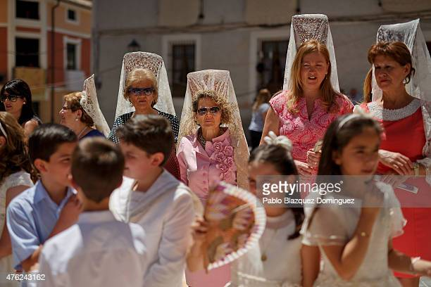 Boys and girls wearing white dress from the communion and women wearing back comb take part in a procession during the Corpus Christi feast on June 7...