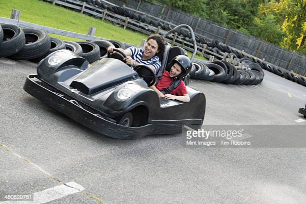 Boys and men go-karting on a track.