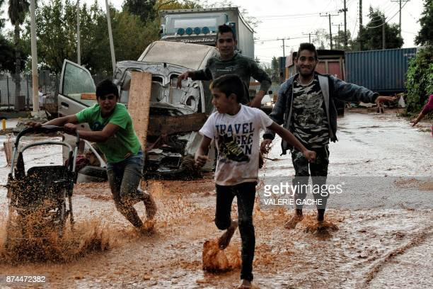 TOPSHOT Boys and young men run through floodwaters in the town of Mandra northwest of Athens on November 15 after heavy overnight rainfall in the...