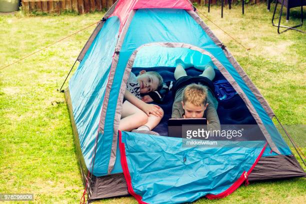 Boys are camping and watching video on digital tablet in a tent