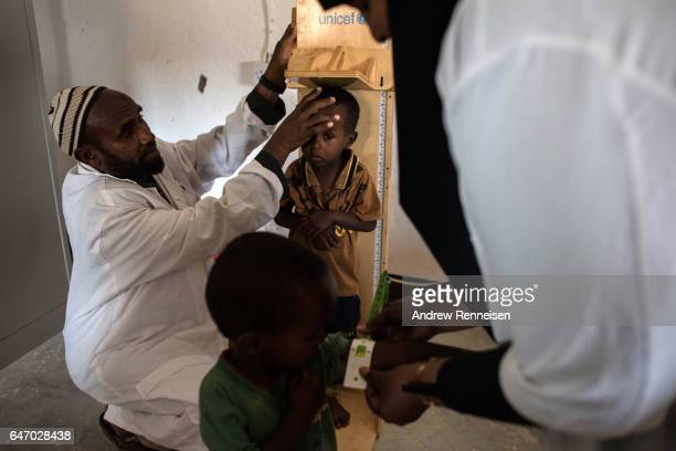 Boys are checked for signs of malnutrition in a government run health clinic on February 25 2017 in Yaka Somalia Somalia is currently on the brink of...
