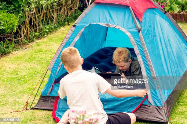 Boys are on camping trip with a tent and one of them watches streaming content on a tablet