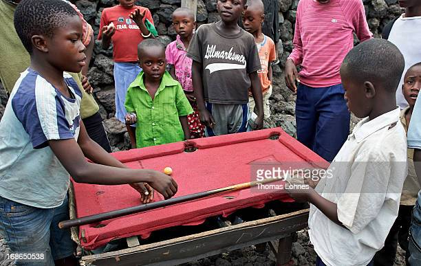 Boys are playing billard on a selfmade billardtable in a game of hazard on January 24 2013 in Goma Democratic Republic of Congo Innumberable...
