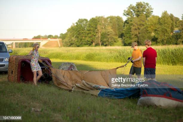 Boys Assisting Pilot In Preparing Hot Air Balloon On Grassy Field Against Sky During Sunset