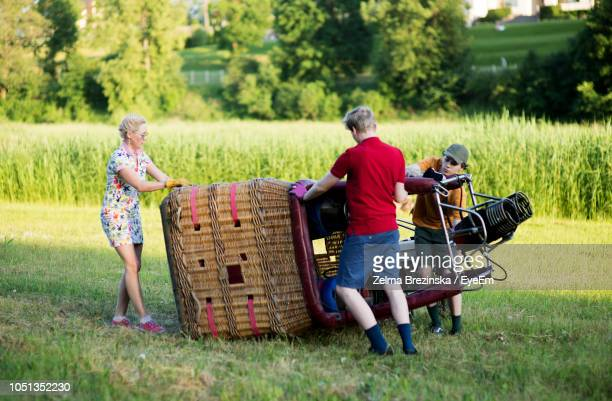 Boys Assisting Pilot In Preparing Hot Air Balloon On Grassy Field During Sunset