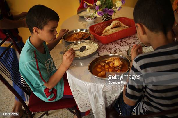 Boys at the Al-Baraum orphanage eat lunch on July 25, 2011 in Baghdad, Iraq. The state owned orphanage has about 50 children currently with the...
