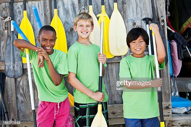 Boys at water sports equipment shack with paddles
