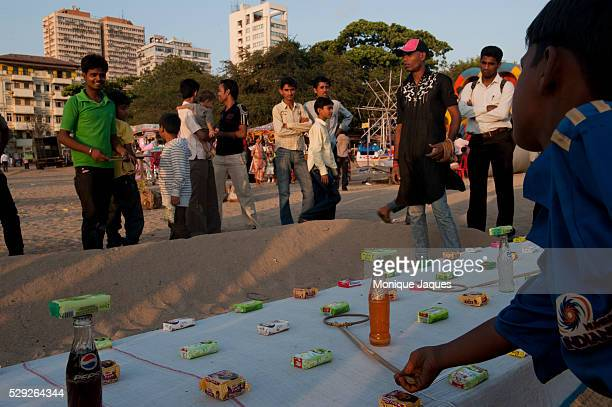 Boys attempt to win bars of soap by throwing rings on bottles of soda pop Locals and tourists visit Chaowpatty Beach in Mumbai Traditionally the site...
