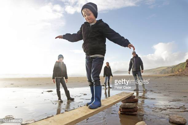 boys balancing on plank of wood, with family on beach - primary age child stock pictures, royalty-free photos & images