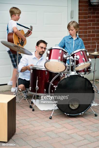 Boy's band getting ready to play in family driveway.