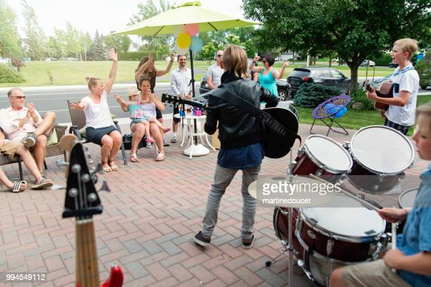 Boy's band in concert in family driveway in summer.