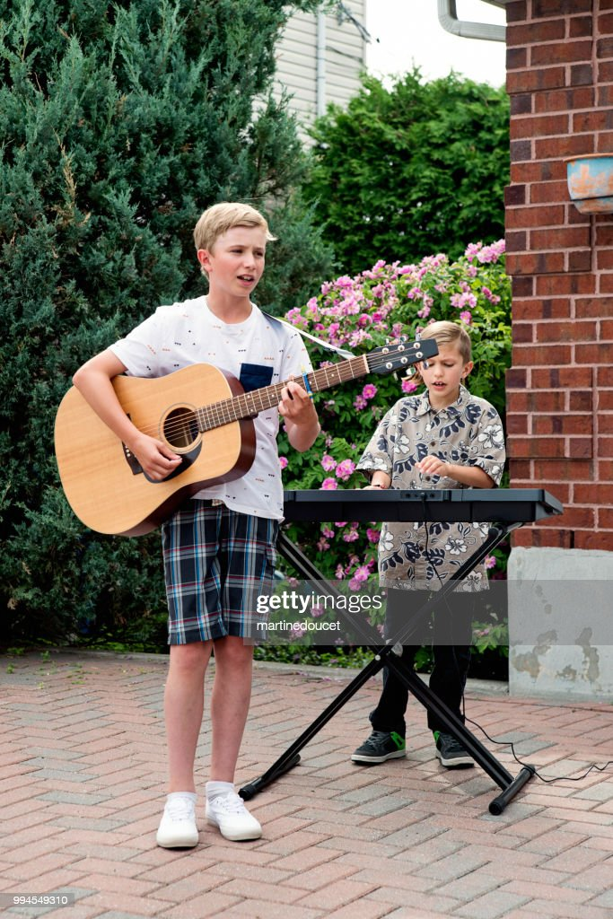 Boy's band in concert in family driveway in summer. : Stock Photo