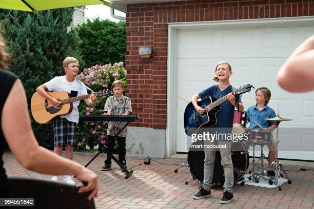 boy's band in concert in family driveway in summer. - garage band stock photos and pictures