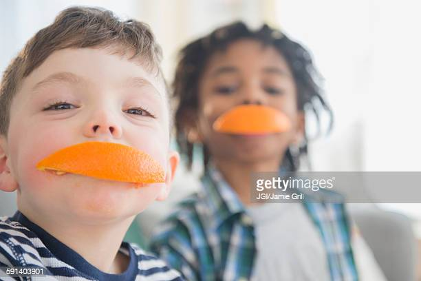 Boys biting orange slices