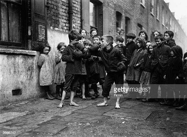 Boys boxing barefoot in a street at Shadwell London watched by a crowd of their friends