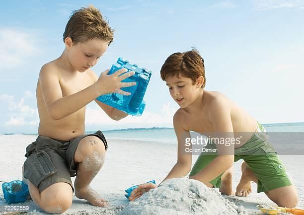Boys building sand castle on the beach