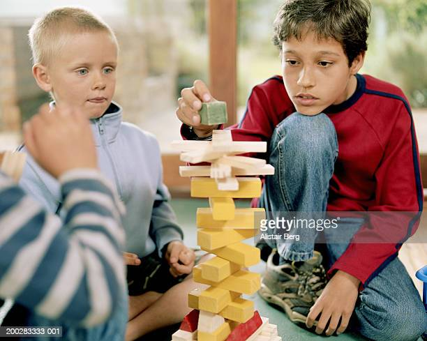 Boys (5-11) building tower from toy building blocks