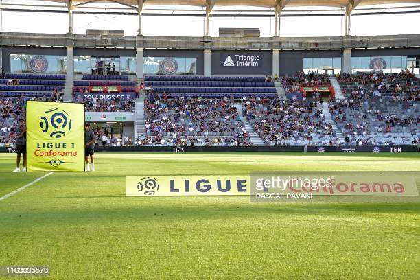 Boys carry a placard bearing the logo of the French first league at the start of the French L1 football match Toulouse against Dijon on August 17,...