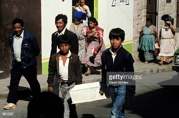 Boys carry a small coffin during a funeral precession in the streets of Quetzaltenango or Xela as the locals call it