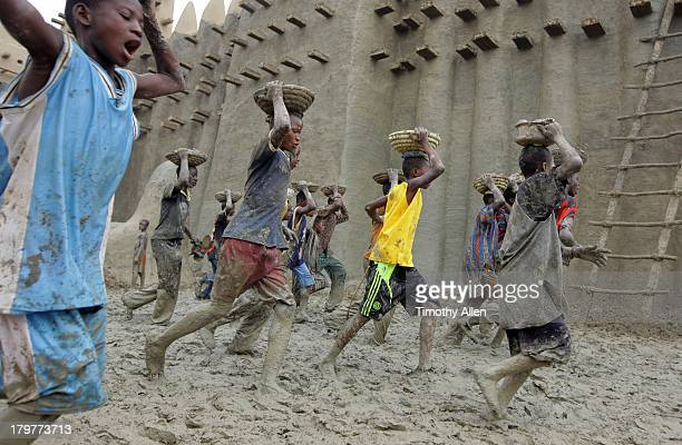 Boys carry mud to Great Mosque, Djenne, Mali