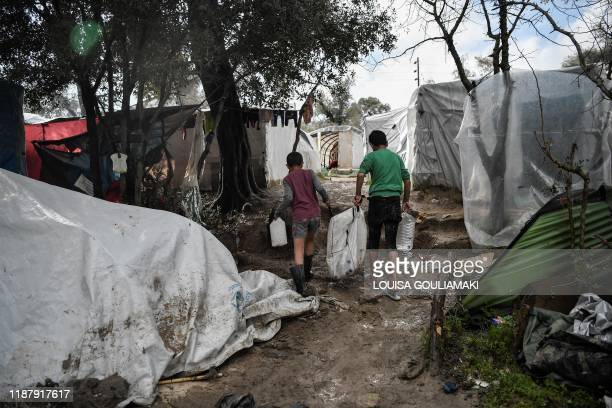 Boys carry water in the makeshift migrant camp after a rainfall hit the island of Chios on December 11 2019 where thousands of refugees and migrants...
