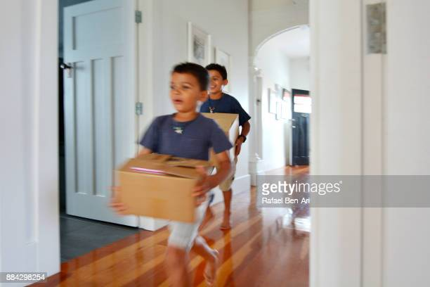 boys carrying moving boxes into their new home - rafael ben ari stockfoto's en -beelden