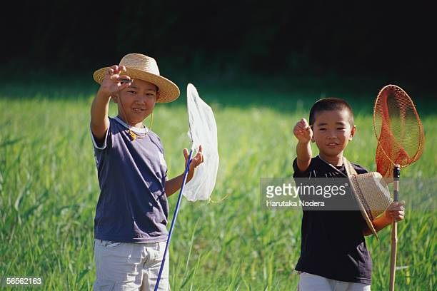 Boys catching insects in field