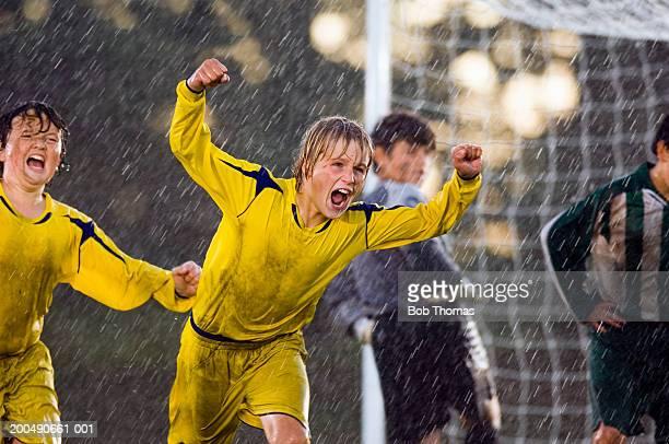 Boys (11-13) celebrating during football game, close-up