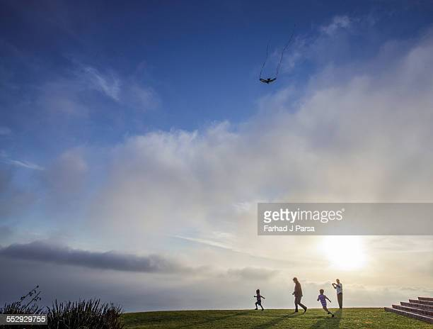 boys chase a high flying kite on lawn - middlebare afstand stockfoto's en -beelden