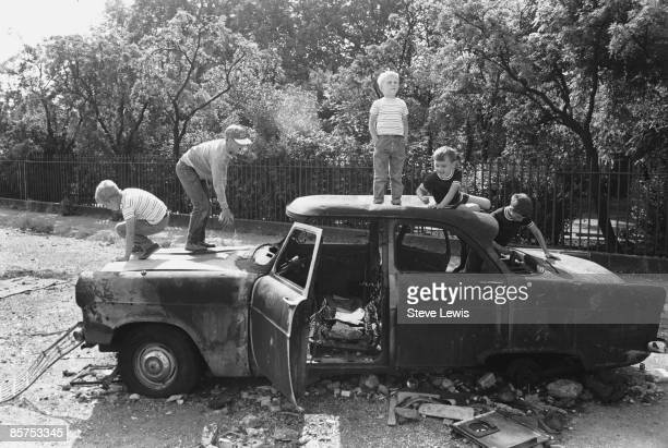 Boys clamber over an abandoned car in the East End of London 1960s