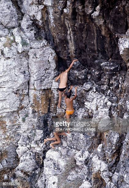 Boys climbing on a cliff near Santa Maria di Leuca Apulia Italy