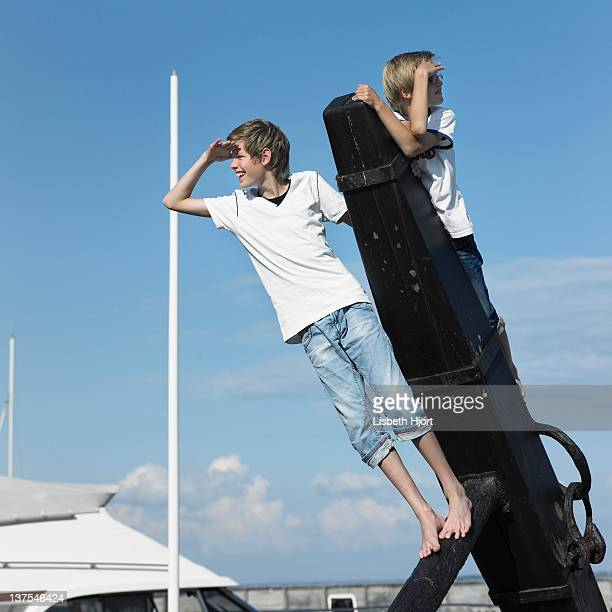 boys climbing on pier - teen boy barefoot stock photos and pictures
