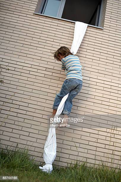 boys climbs out of window using sheet rope - escapism stock pictures, royalty-free photos & images