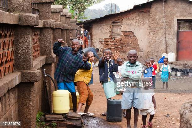 boys collecting water in african slum - global village stock pictures, royalty-free photos & images