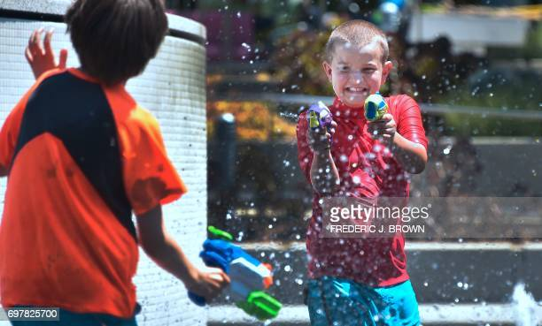 Boys cool of with water guns at the Grand Park splash pad in downtown Los Angeles California on June 19 amid a Southern California heatwave with...