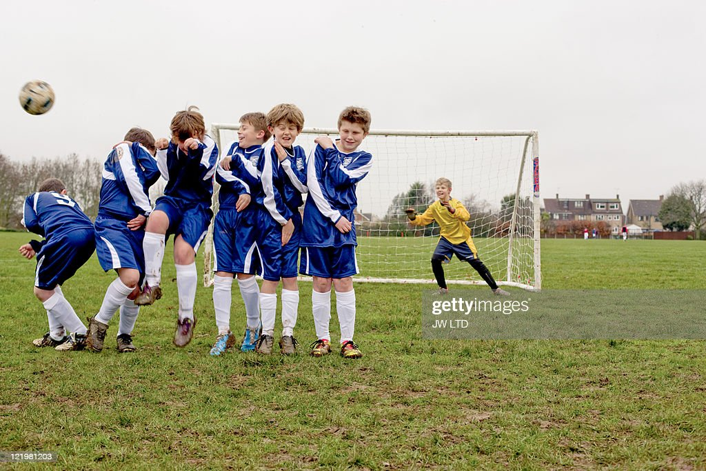 Boys defending free kick during football game : Stock Photo