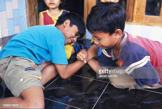 FAMILY LIFE INDONESIA Boys doing a traditional arm wrestling match in a village in East Java CDREF00141