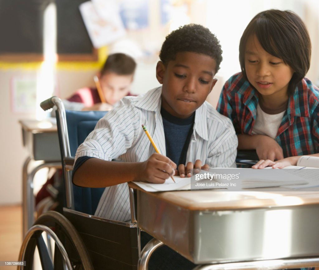 Boys doing schoolwork together : Stock Photo