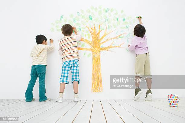Boys drawing a tree, rear view